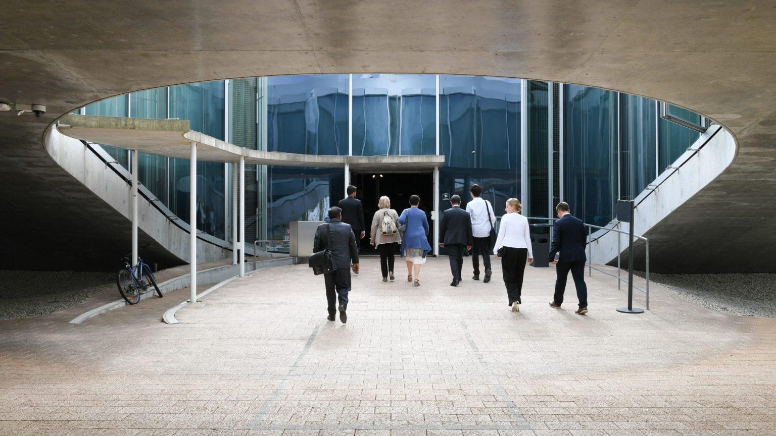 Des personnes, de dos, entrant dans le Rolex Learning Center